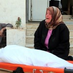 A woman grieves outside a northern Syria hospital where her son's body was brought after he was killed by a sniper. The deceased, an unarmed civilian, was shot in the head as he stood on a highway while waiting for a ride. The mother was crying, shouting